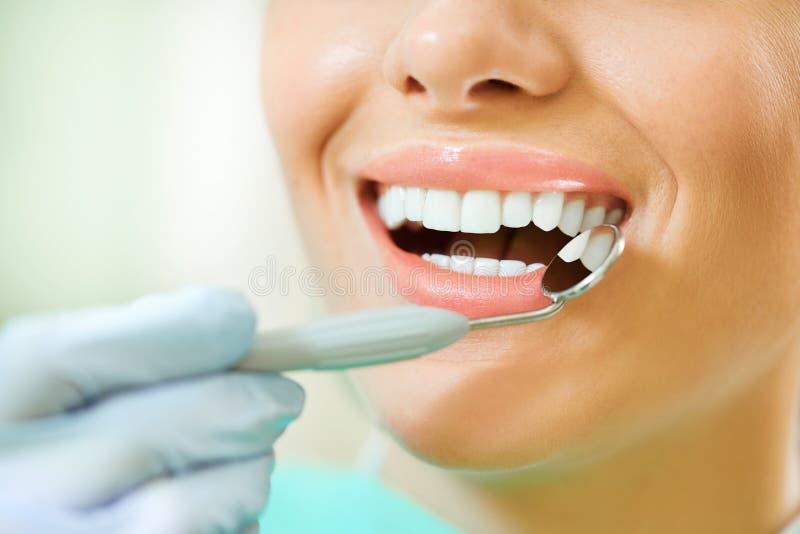 Dentes da mulher e um espelho de boca do dentista fotos de stock royalty free