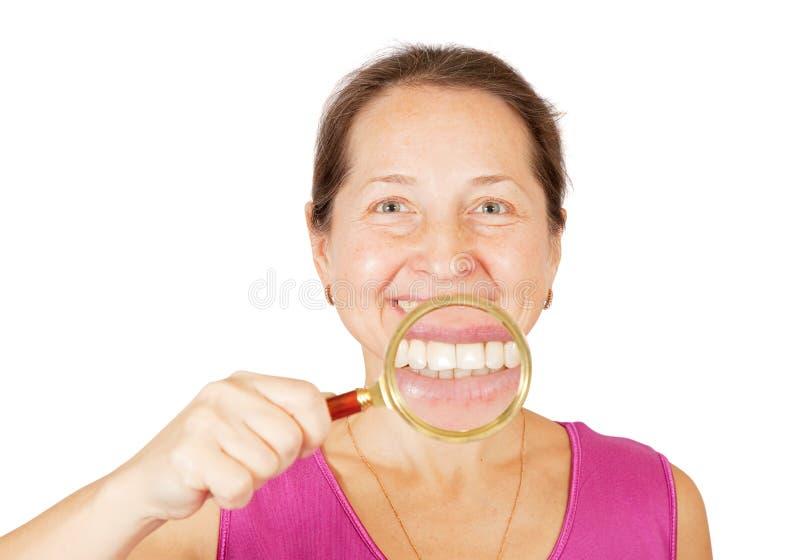 Dentes da mulher madura através do magnifie imagem de stock