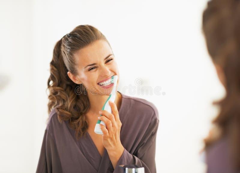 Dentes de escovadela da jovem mulher feliz imagem de stock royalty free