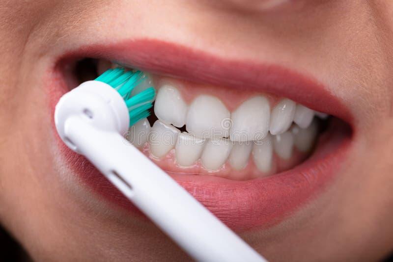 Dentes de escovadela da mulher com toothbrush el?trico fotos de stock