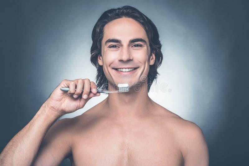 Dentes de escovadela do homem foto de stock