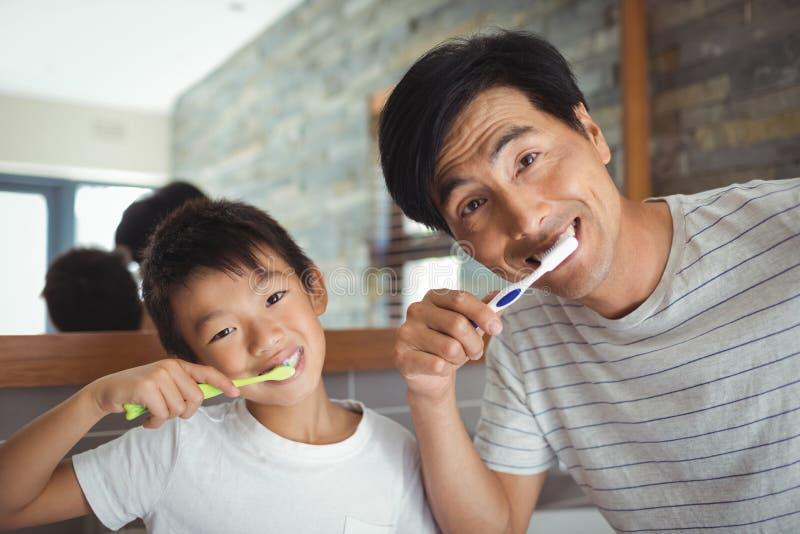 Dentes de escovadela do pai e do filho no banheiro fotografia de stock royalty free