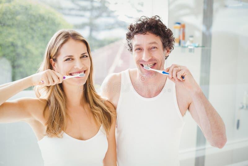 Dentes de escovadela dos pares felizes fotografia de stock royalty free