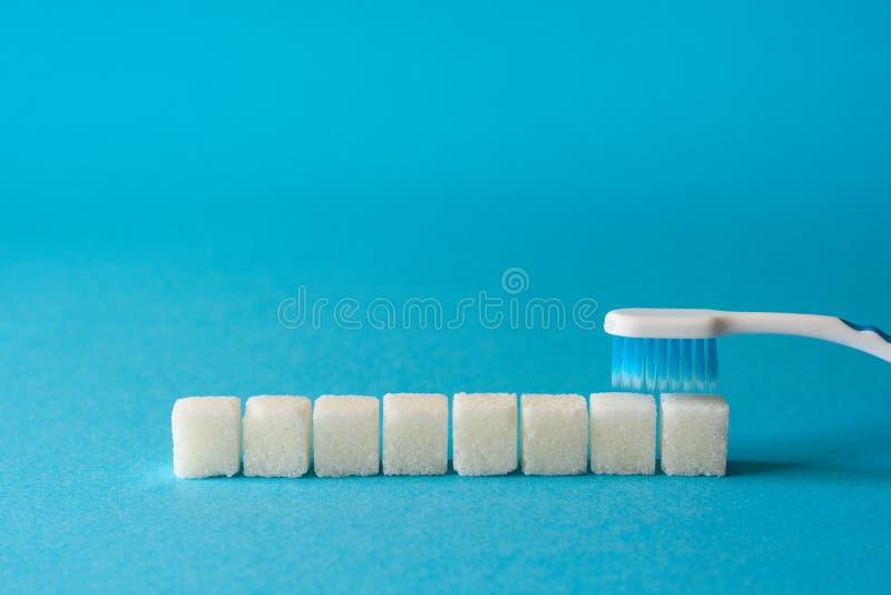Dentes de escovadela A escova de dentes limpa a sujeira dos dentes Alegoria dos cubos do açúcar e das sementes de sésamo Conceito imagens de stock