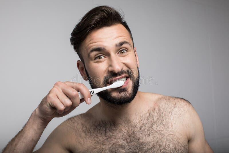 dentes de escovadela farpados consideráveis do homem novo e vista da câmera foto de stock