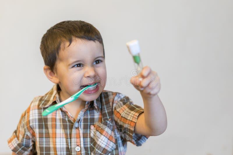 Dentes de escovadela na sala do banho, pyjamas vestindo do rapaz pequeno do retrato da criança com limpeza de seus dentes na manh foto de stock royalty free