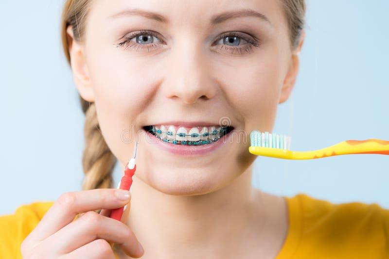 Dentes de sorriso da limpeza da mulher com cintas imagem de stock royalty free