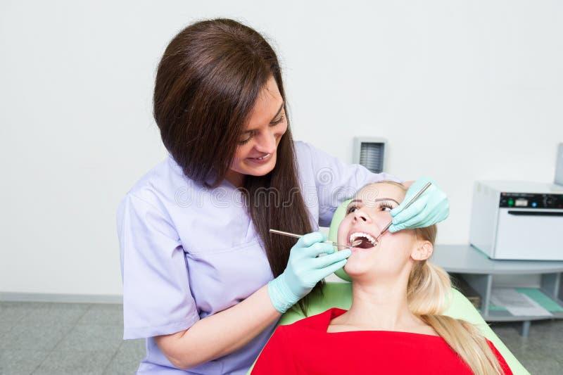 Dentes de verificação e de limpeza da mulher amigável do dentista fotos de stock royalty free