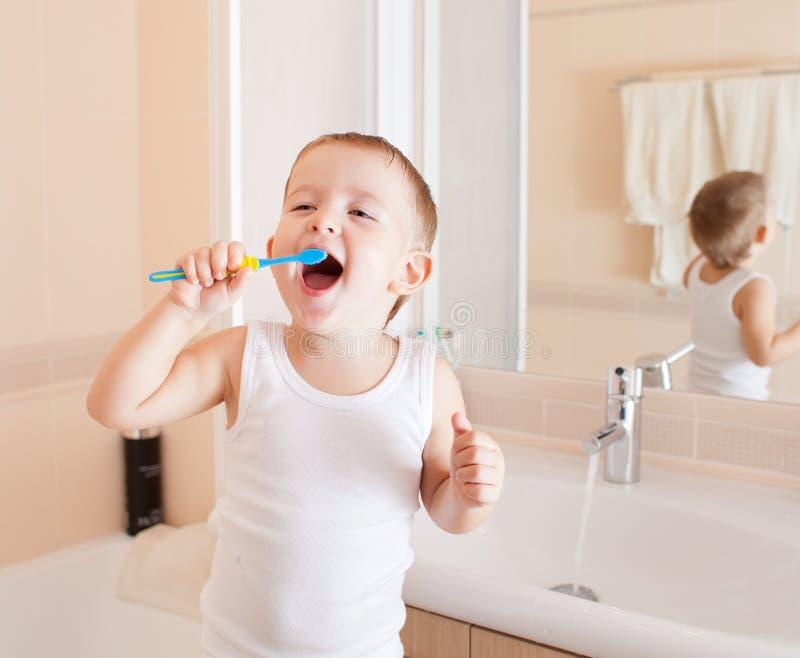 Dentes engraçados da limpeza do menino do miúdo no banheiro imagens de stock royalty free