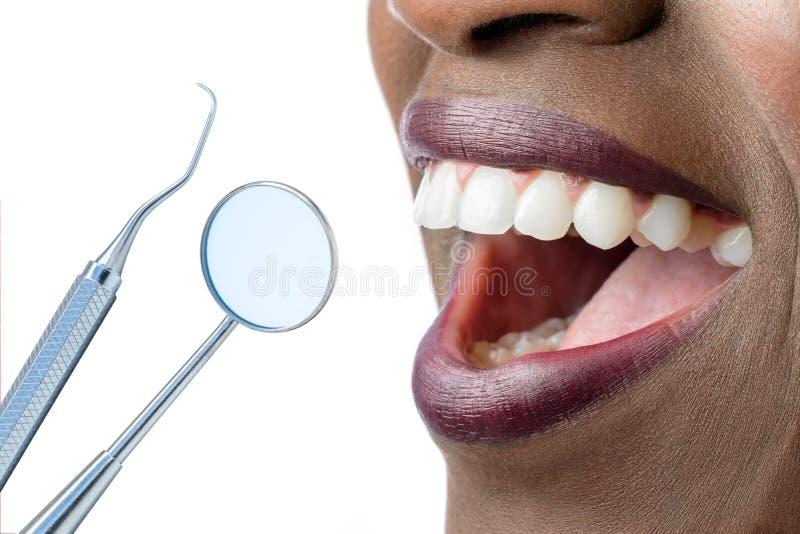 Dentes fêmeas africanos com machado e espelho de boca imagem de stock
