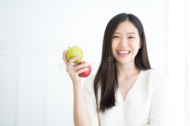Dentes fortes da mostra asiática nova da maçã do verde da mordida da mulher foto de stock royalty free