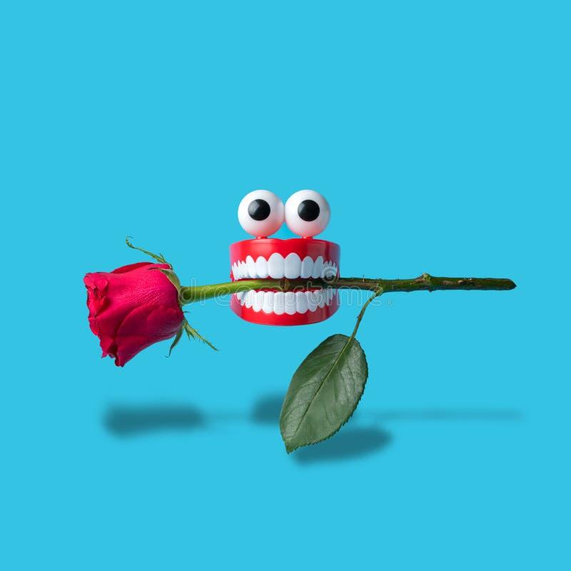 Dentes plásticos do brinquedo com a flor cor-de-rosa no fundo azul Composi??o m?nima abstrata imagens de stock royalty free