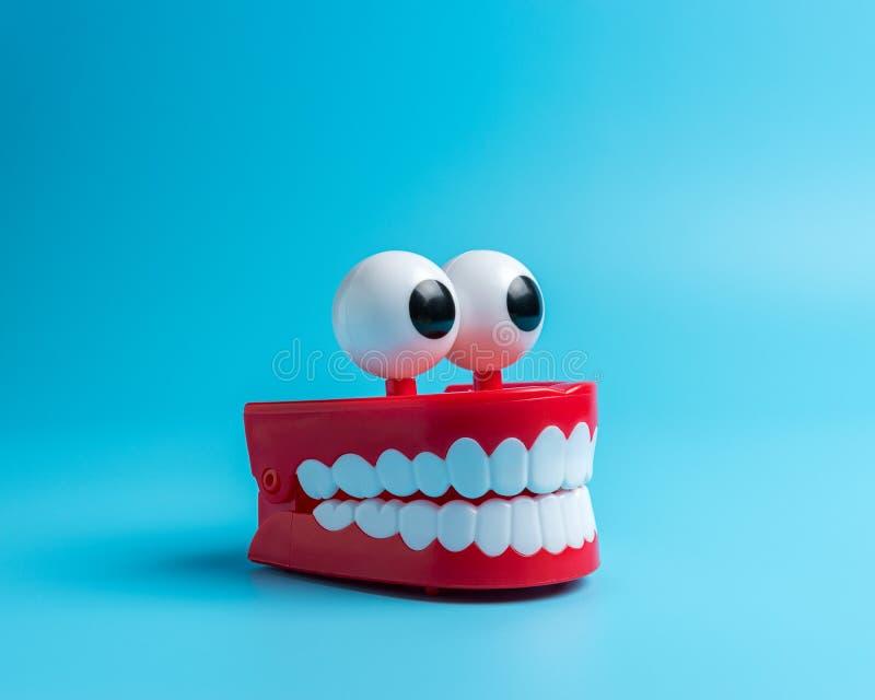 Dentes plásticos do brinquedo no fundo azul Composi??o m?nima abstrata imagem de stock royalty free