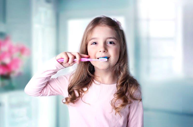 Denti caucasici di pulizia della ragazza del bambino in bagno immagini stock libere da diritti