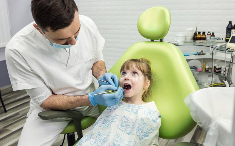 Denti d'esame del ` s della bambina del dentista in clinica Problema dentario fotografia stock