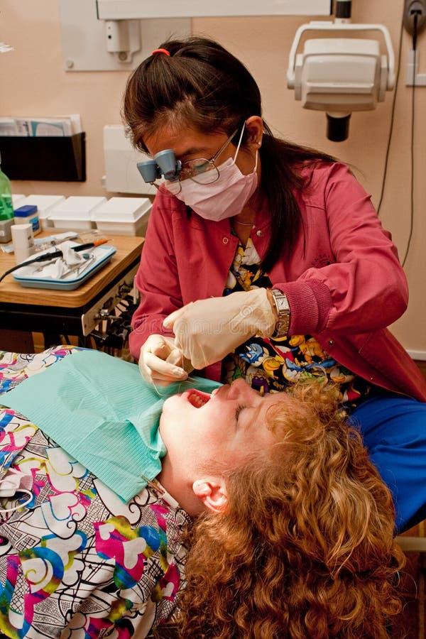 Denti del paziente di pulizia dell'igienista dentale immagine stock