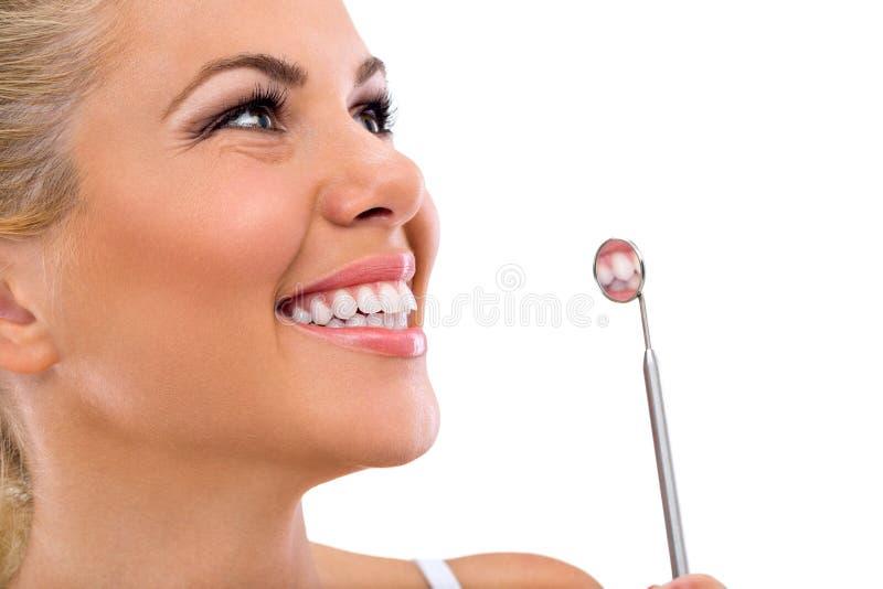 Denti della donna e uno specchio del dentista immagini stock