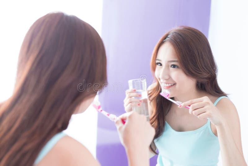 Denti della spazzola della donna di sorriso fotografia stock