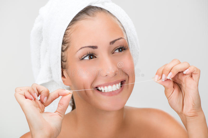 Denti di pulizia con filo per i denti immagine stock libera da diritti