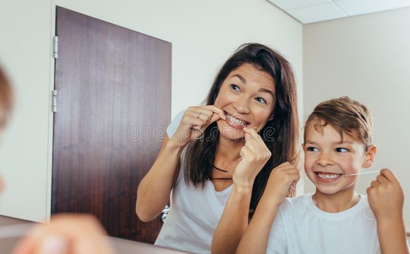Denti di pulizia del figlio e della madre con filo per i denti immagine stock