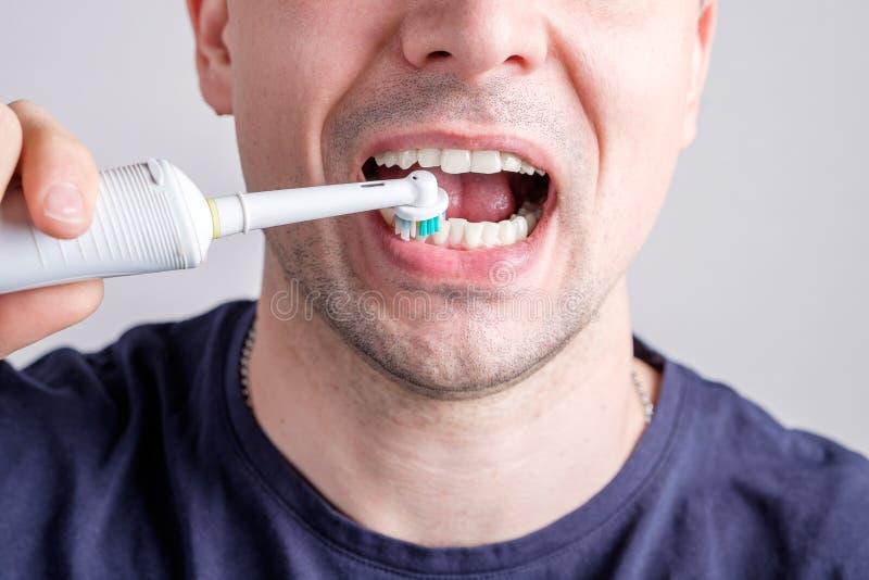 Denti di pulizia dell'uomo con lo spazzolino da denti elettrico fotografia stock