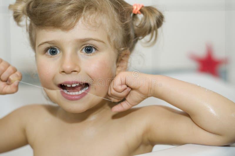 Denti di pulizia della bambina da filo di seta fotografia stock libera da diritti