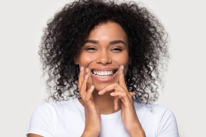 Denti di pulizia della donna africana felice del ritratto del primo piano con filo per i denti immagine stock libera da diritti