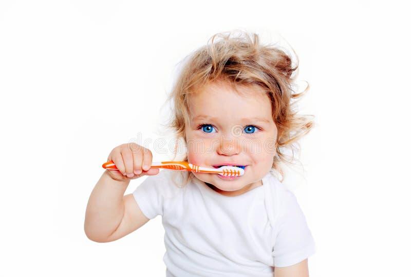 Denti di spazzolatura del bambino riccio del bambino immagini stock
