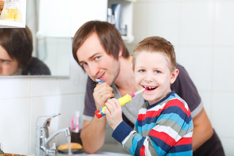 Denti di spazzolatura del figlio e del padre immagine stock libera da diritti