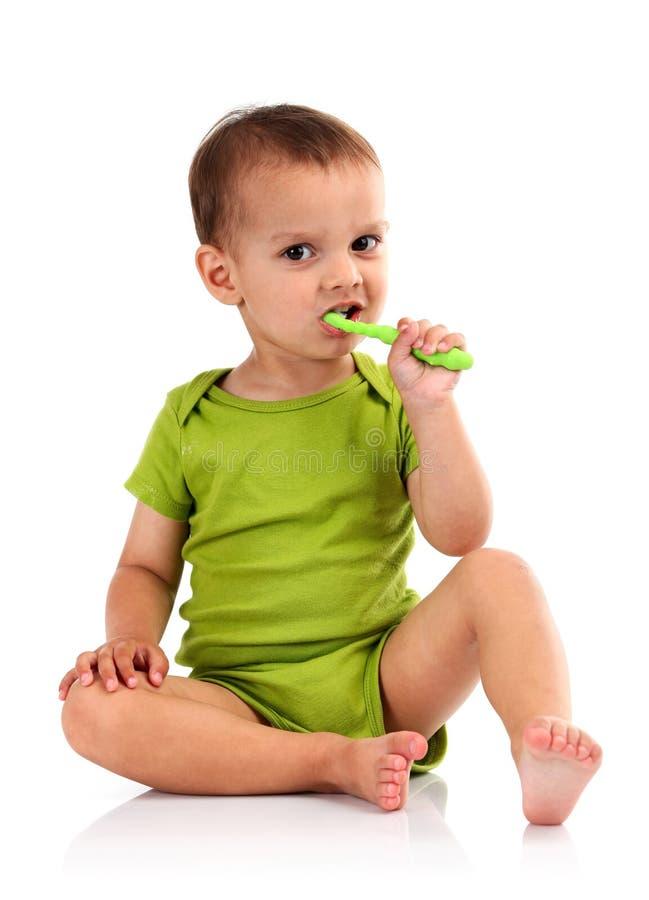 Denti di spazzolatura del ragazzino sveglio, isolati su bianco immagini stock libere da diritti