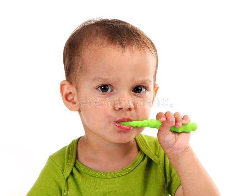Denti di spazzolatura del ragazzino sveglio, isolati su bianco immagine stock