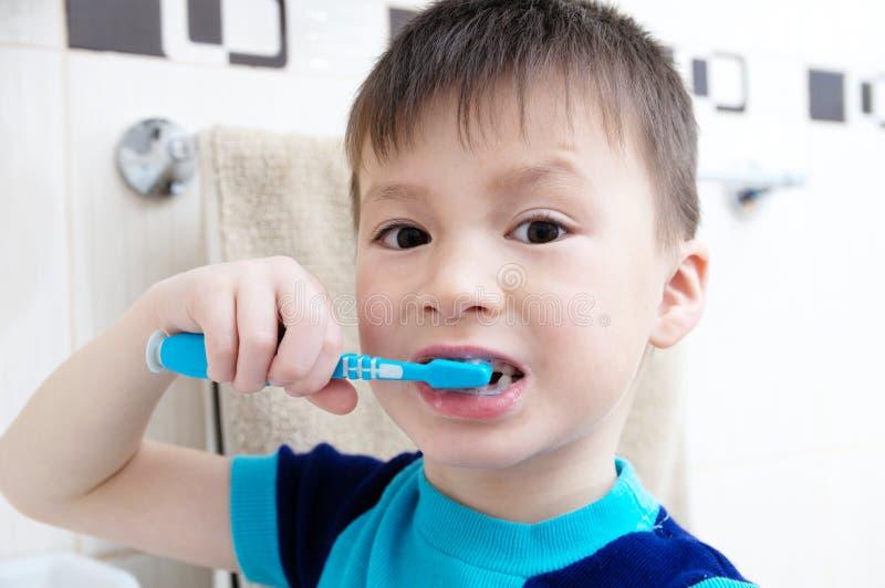 Denti di spazzolatura del ragazzo, cure odontoiatriche del bambino, concetto di igiene orale, ritratto del bambino in bagno con l fotografia stock