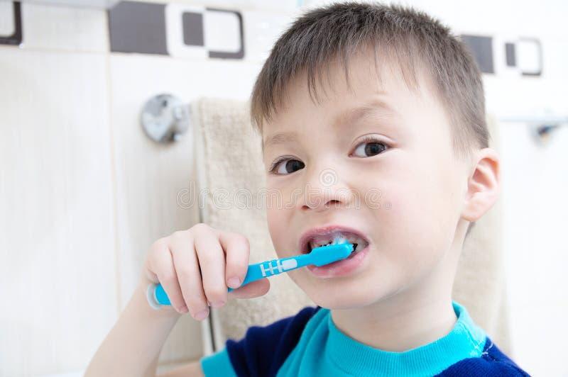 Denti di spazzolatura del ragazzo, cure odontoiatriche del bambino, concetto di igiene orale, ritratto del ragazzo in bagno con l fotografie stock