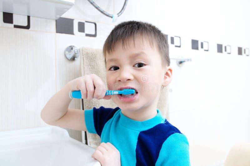 Denti di spazzolatura del ritratto del bambino, cure odontoiatriche del ragazzo, concetto di igiene orale, bambino in bagno con l fotografia stock libera da diritti