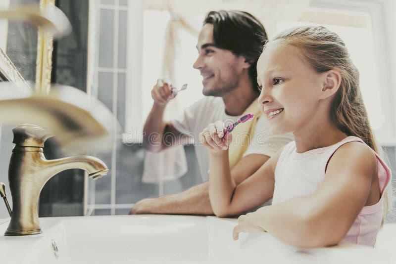 Denti di spazzolatura dell'uomo bello e della ragazza sveglia a casa fotografie stock
