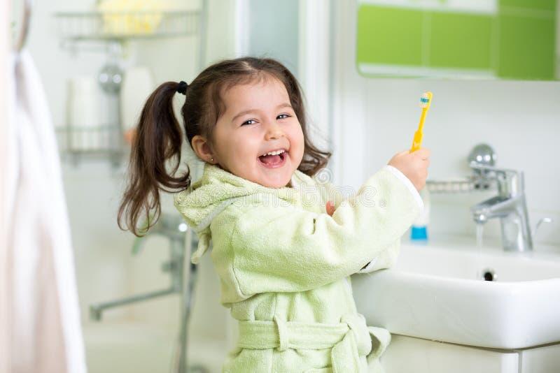 Denti di spazzolatura della bambina nel bagno immagine stock