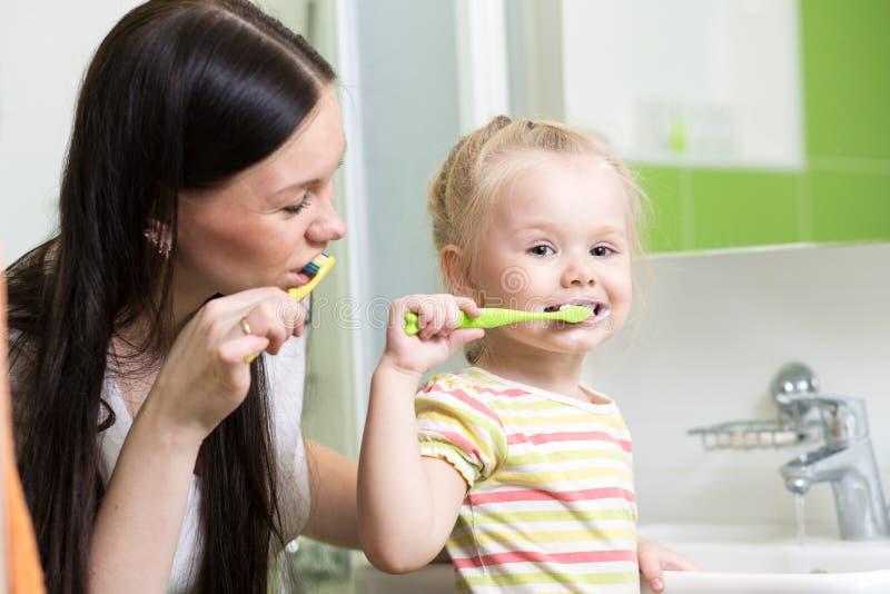 Denti di spazzolatura della figlia del bambino e della madre insieme in bagno immagini stock