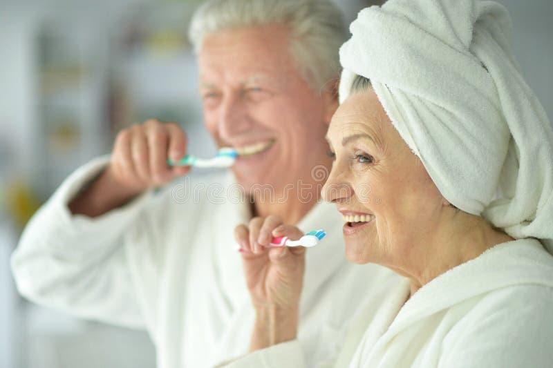 Denti di spazzolatura delle coppie senior felici immagini stock libere da diritti