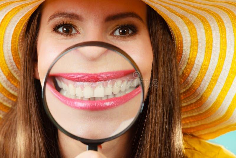 Denti divertenti di manifestazione della donna tramite la lente d'ingrandimento fotografie stock