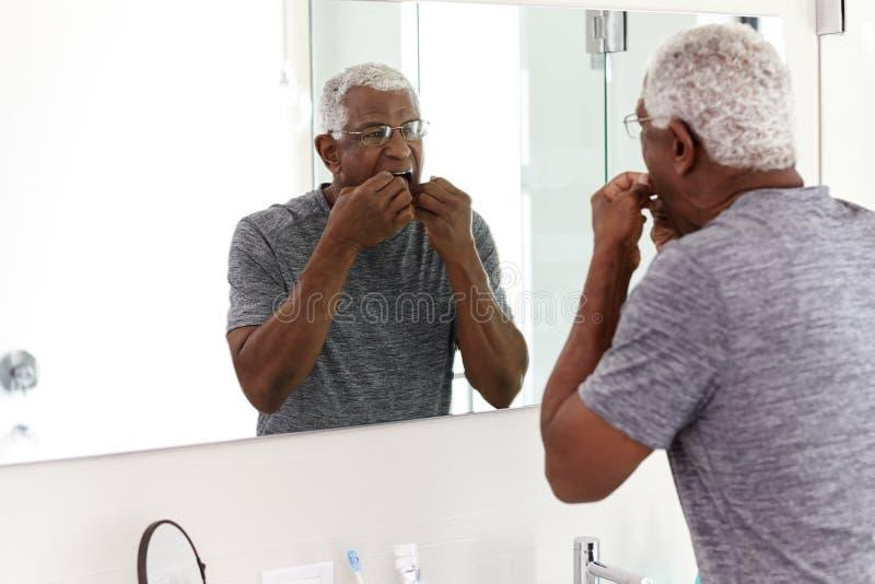 Denti Flossing dell'uomo senior che esaminano riflessione in pigiami d'uso dello specchio del bagno fotografia stock