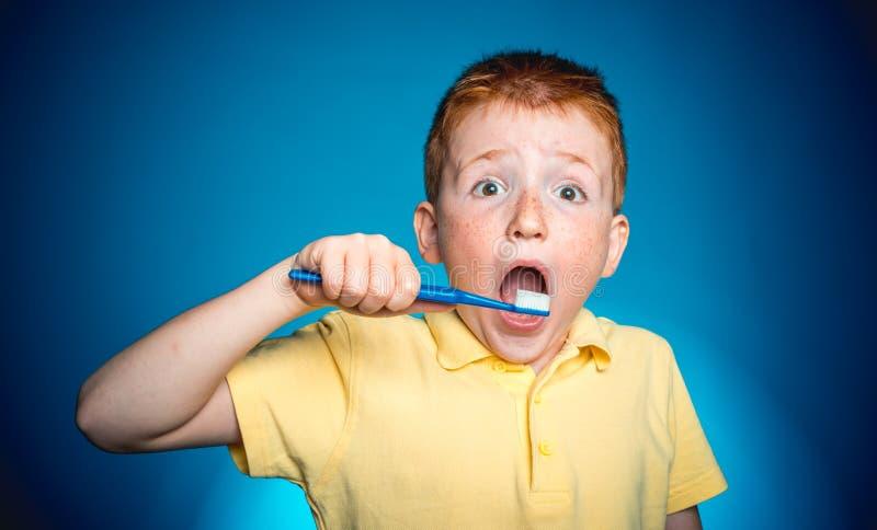 Denti puliti del bambino con lo spazzolino da denti Bambino con lo spazzolino da denti isolato su fondo blu Il ragazzo dai capell immagine stock