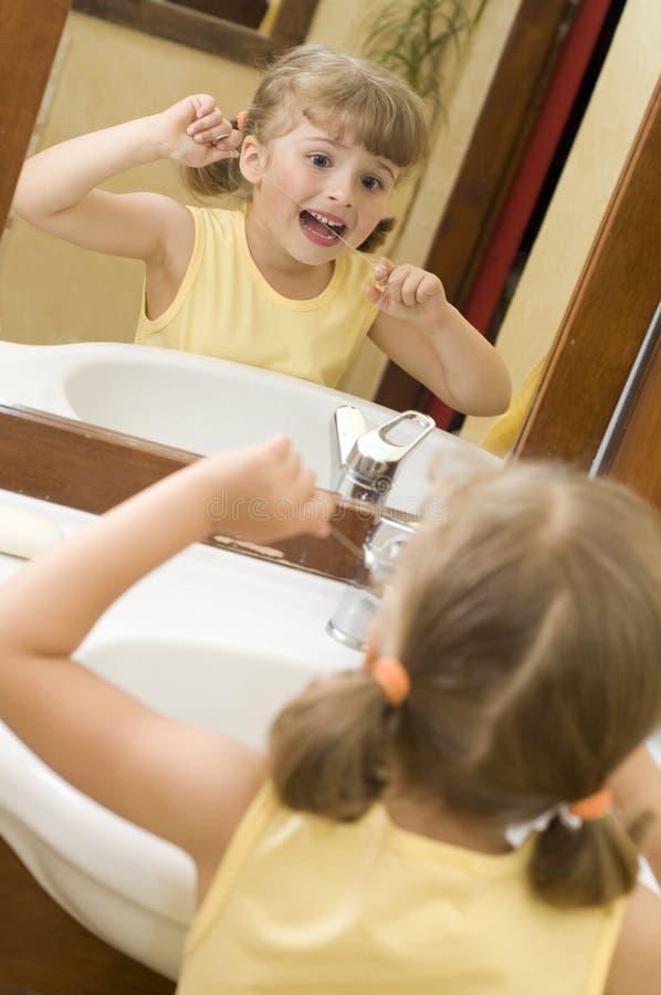 Denti svegli di pulizia della ragazza da filo di seta fotografie stock libere da diritti