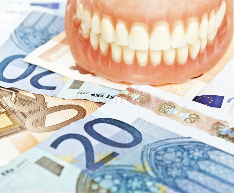 Dentier sur des euros - concept dentaire de dépenses images libres de droits