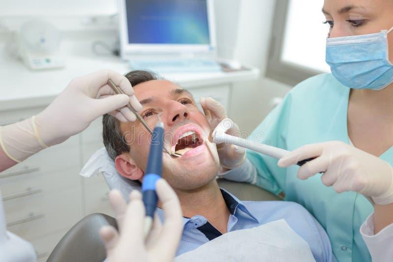 Dentis femelles fonctionnant avec le patient au bureau dentaire de clinique image libre de droits