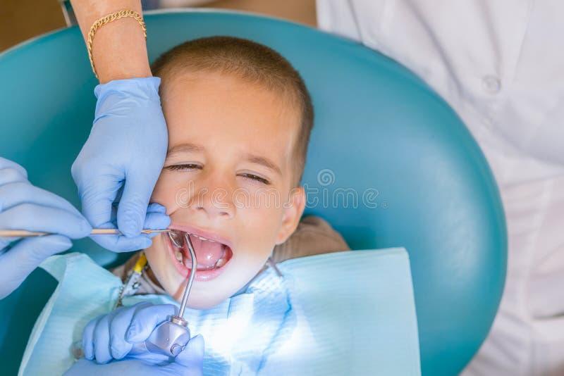dentist&的x27一个小男孩;一个牙齿诊所的s招待会 Children& x27; s牙科,小儿科牙科 一位女性 免版税库存照片