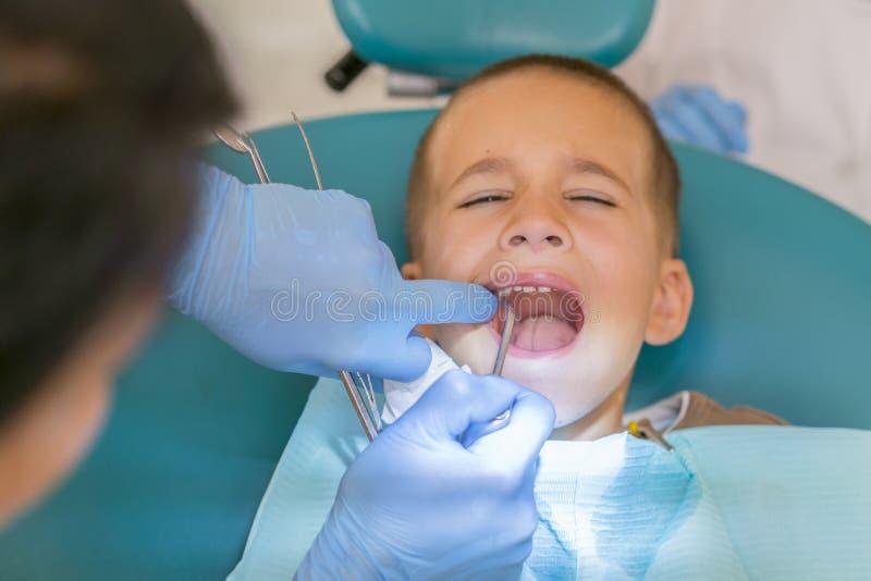 dentist&的x27一个小男孩;一个牙齿诊所的s招待会 Children& x27; s牙科,小儿科牙科 一位女性 库存图片