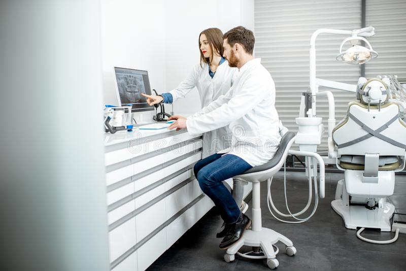 Dentist with assistant in the dental office. Dentist with young women assistant working with computer in the dental office royalty free stock photos