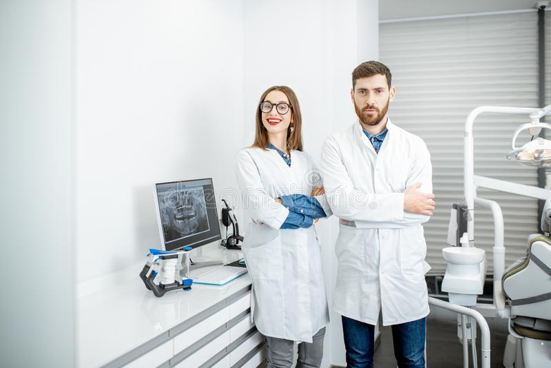 Dentist with assistant in the dental office. Portrait of a dentist with young women assistant in white medical gowns standing in the dental office royalty free stock image