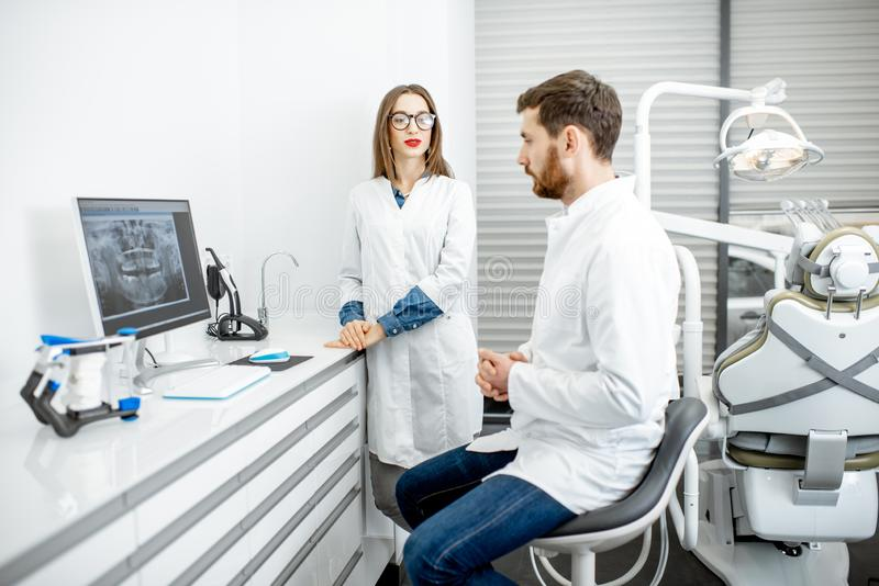 Dentist with assistant in the dental office. Dentist with young women assistant working with computer in the dental office royalty free stock image