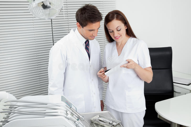 Dentist And Assistant With Dental Report. Male dentist with assistant discussing dental report in clinic royalty free stock images